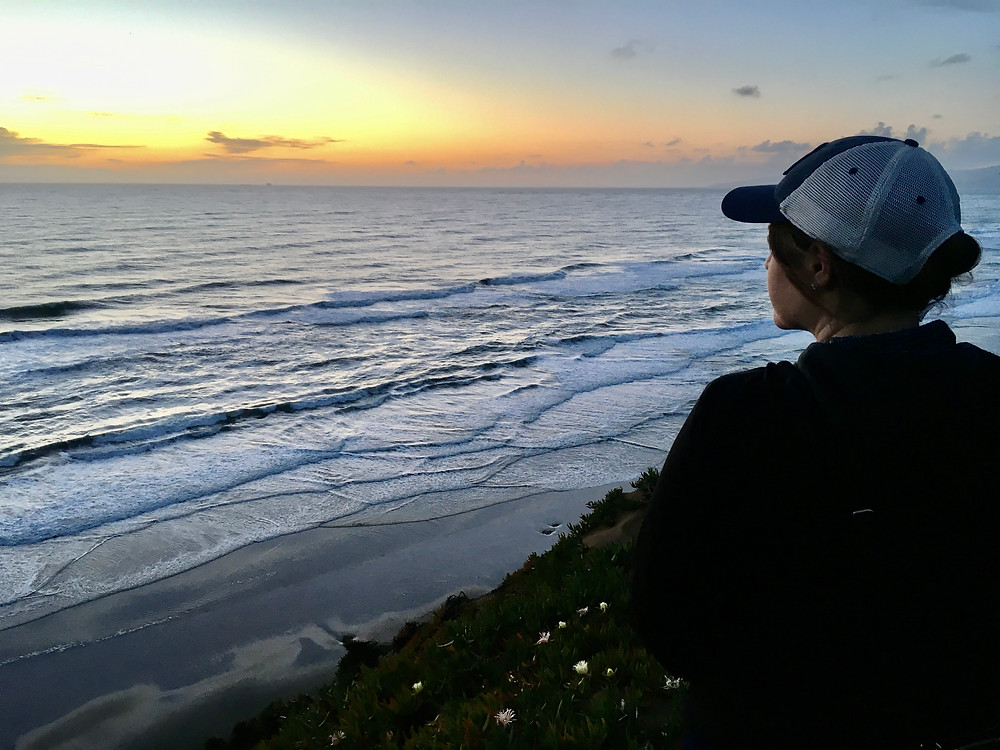 A woman wearing a Red Sox trucker hat, sitting on a cliff by the shore of the Pacific Ocean, looking off into the brilliant orange sunset over the waters of Point Reyes National Seashore in CAlifornia