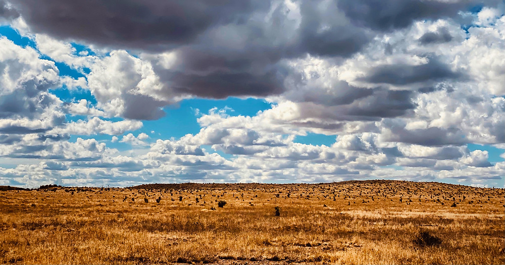 white and grey clouds partially obscure a brilliant blue sky over the brownish scrubland plains of Texas