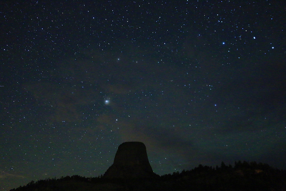 The blue-black night sky is brilliantly illuminated with countless stars over Devil's Tower in Wyoming