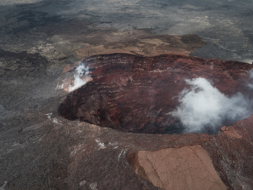 An overhead view of a volcano, steam rising from the rim of the caldera