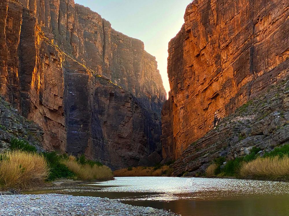 The mighty Rio Grande cuts through a reddish orange slot canyon in Big Bend National Park, Texas