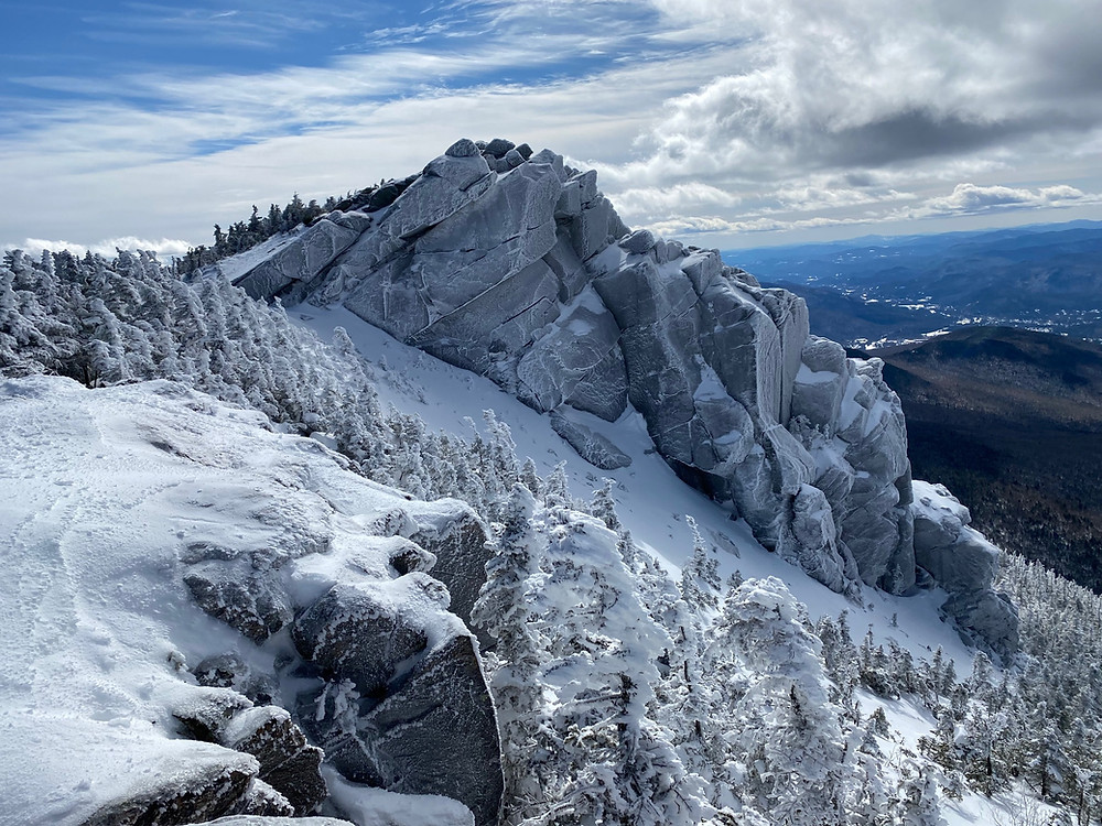 a beautiful view from the mountaintops of the Presidential Range, White Mountains National Forest. A craggy mountain looms over pine trees covered in snow. Clouds partially obscure the striking blue sky