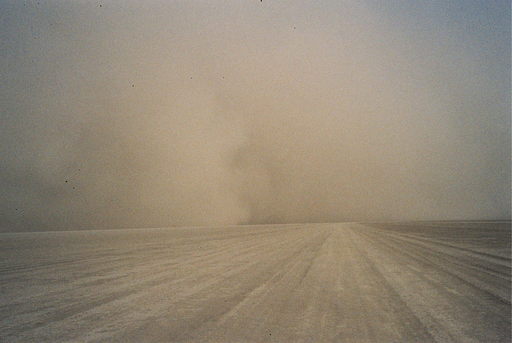 a dust and mud storm, also known as a haboob, obscures the road, the skies, and the entire area in a brown haze