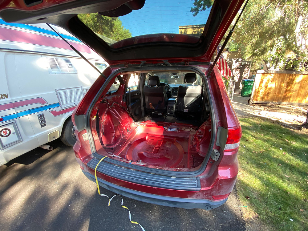 a red 2011 Jeep Grand Cherokee begins its transformation from soccer-mobile to a camper for Van Life. Here, the rear interior is completely hollowed out.