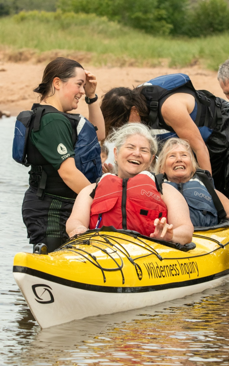 two older women laugh and smile in a yellow kayak as they are set up for the waterways by Wilderness Inquiry staff