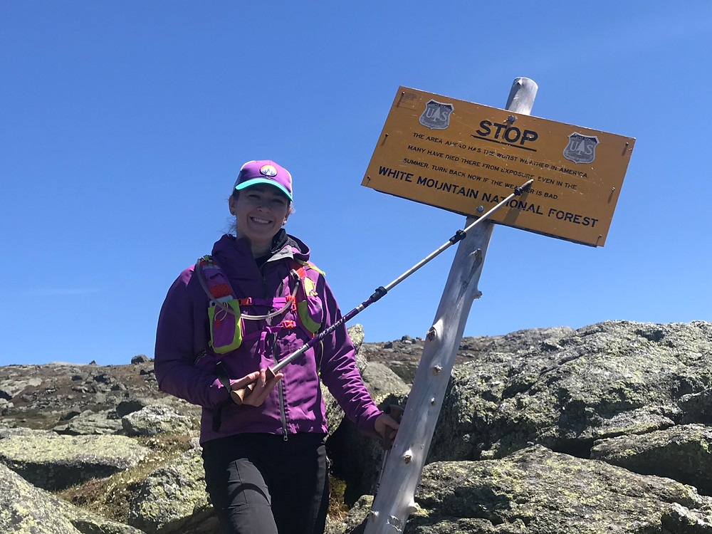 A woman in purple hiking gear nears the summit of Mount Washington, using her hiking pole to point out that this region of the White Mountains National Forest in New Hampshire  is known for having some of the worst weather in the world