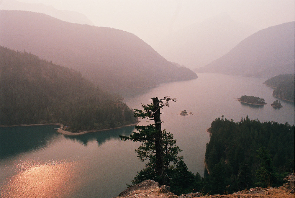 the eerie, creepy, spooky, ooky Diablo Lake in North Cascades National Park. Smoke from nearby wildfires lays a sinister haze over the terrain, with mountains diving deep into the lake