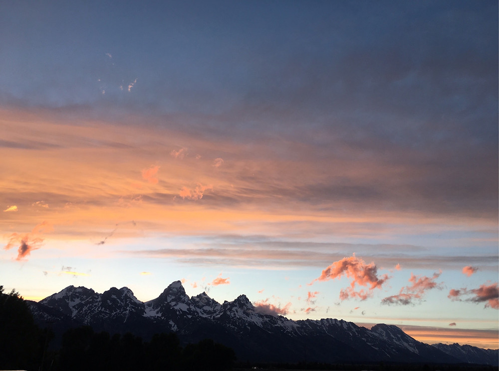 Pink skies over snow capped mountains at Grand Teton National Park in Wyoming