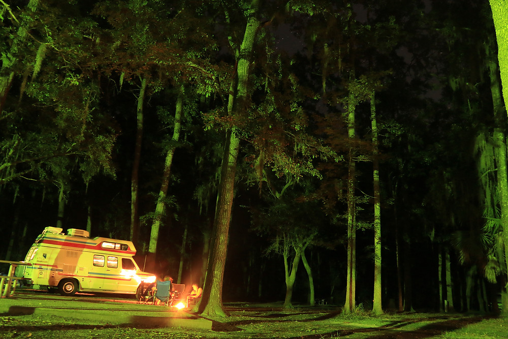 """The """"Spirit of the West"""" has pulled into a dark green forest at night. Some campers have set up just outside the van, sitting in chairs around a fire in Fort McAllister State Park near Savannah, Georgia"""