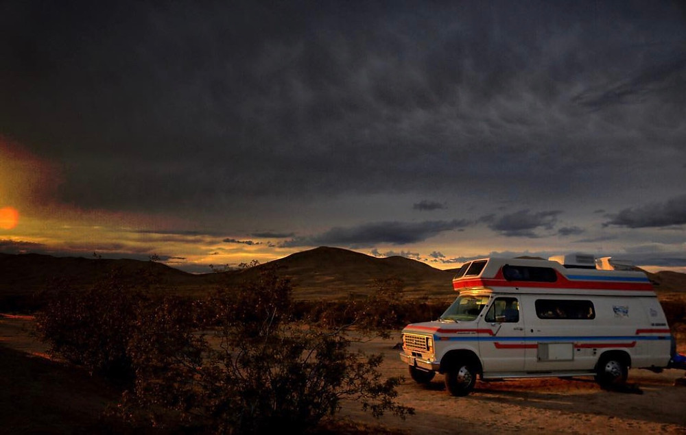 The Spirit of the West van parked in the desert in front of a mountain range, with stormy skies overhead obscuring the setting sun