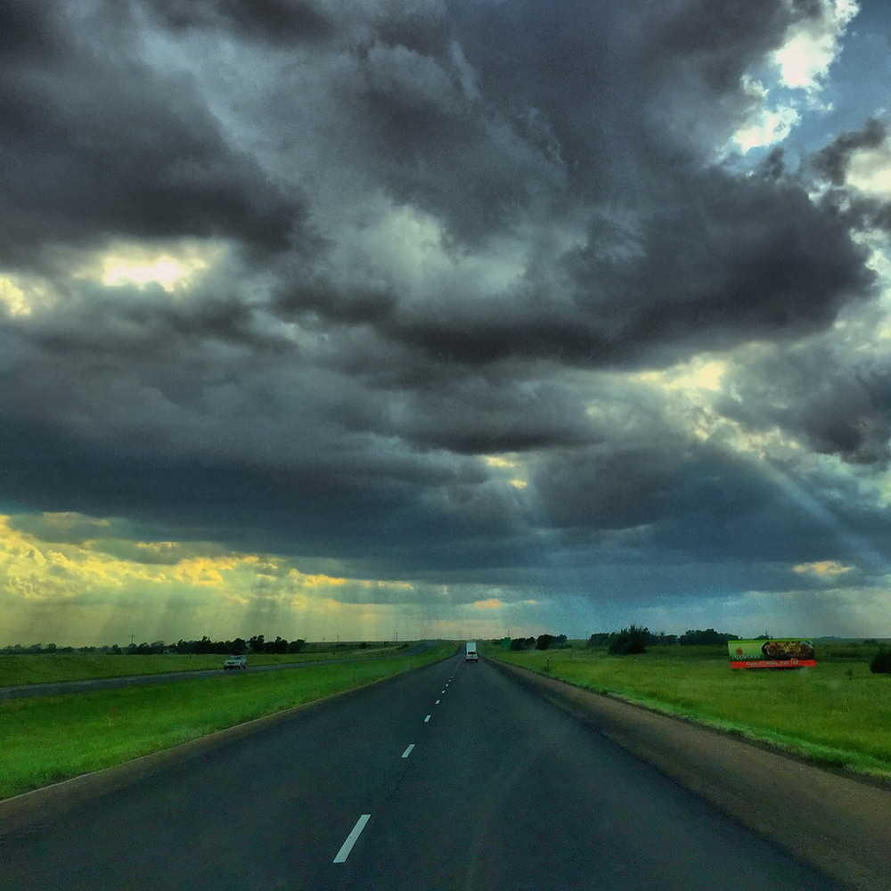 The sun desperately tries to shine through a massive overhead storm cloud above a long highway through Arkansas