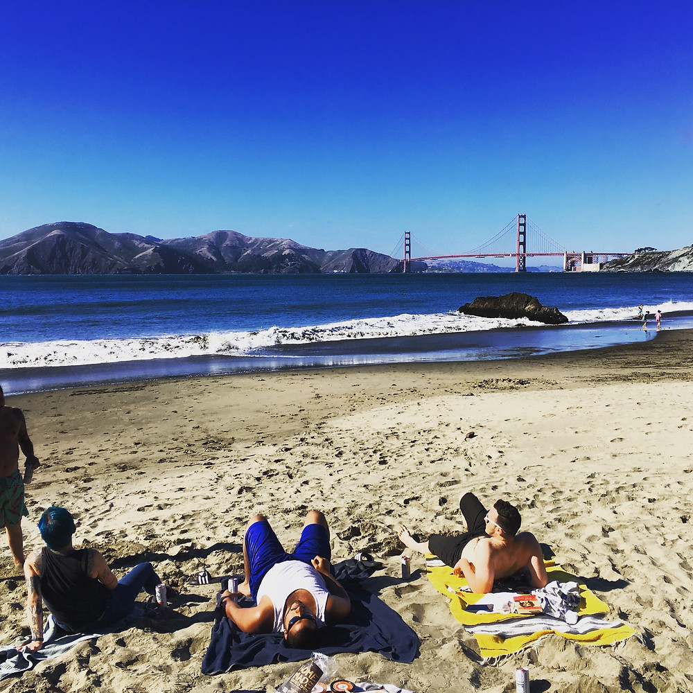 Some people lay out in the sun at China Beach in San Francisco, with a spectacular view of the Golden Gate Bridge and Marin County across the bay