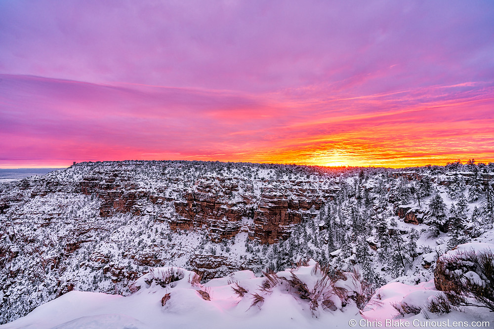 Pinks, purples, oranges, reds, and yellows illuminate the sky at sunset over the snowy Grand Canyon in Arizona