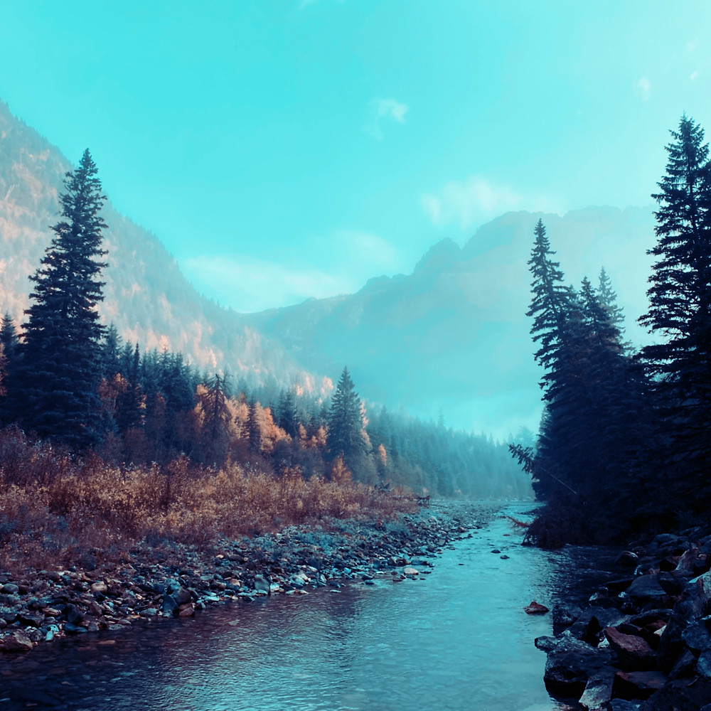 A haze sets in over a beautiful wooded river in Glacier National Park, Utah