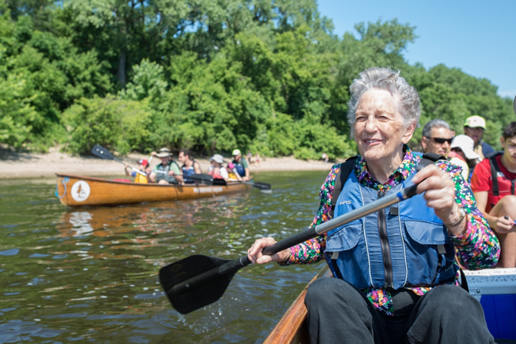 An older woman smiles as she paddles a large canoe full of people down the Mississippi River. A smaller orange kayak floats nearby, just offshore from a sandy beach and lush green trees