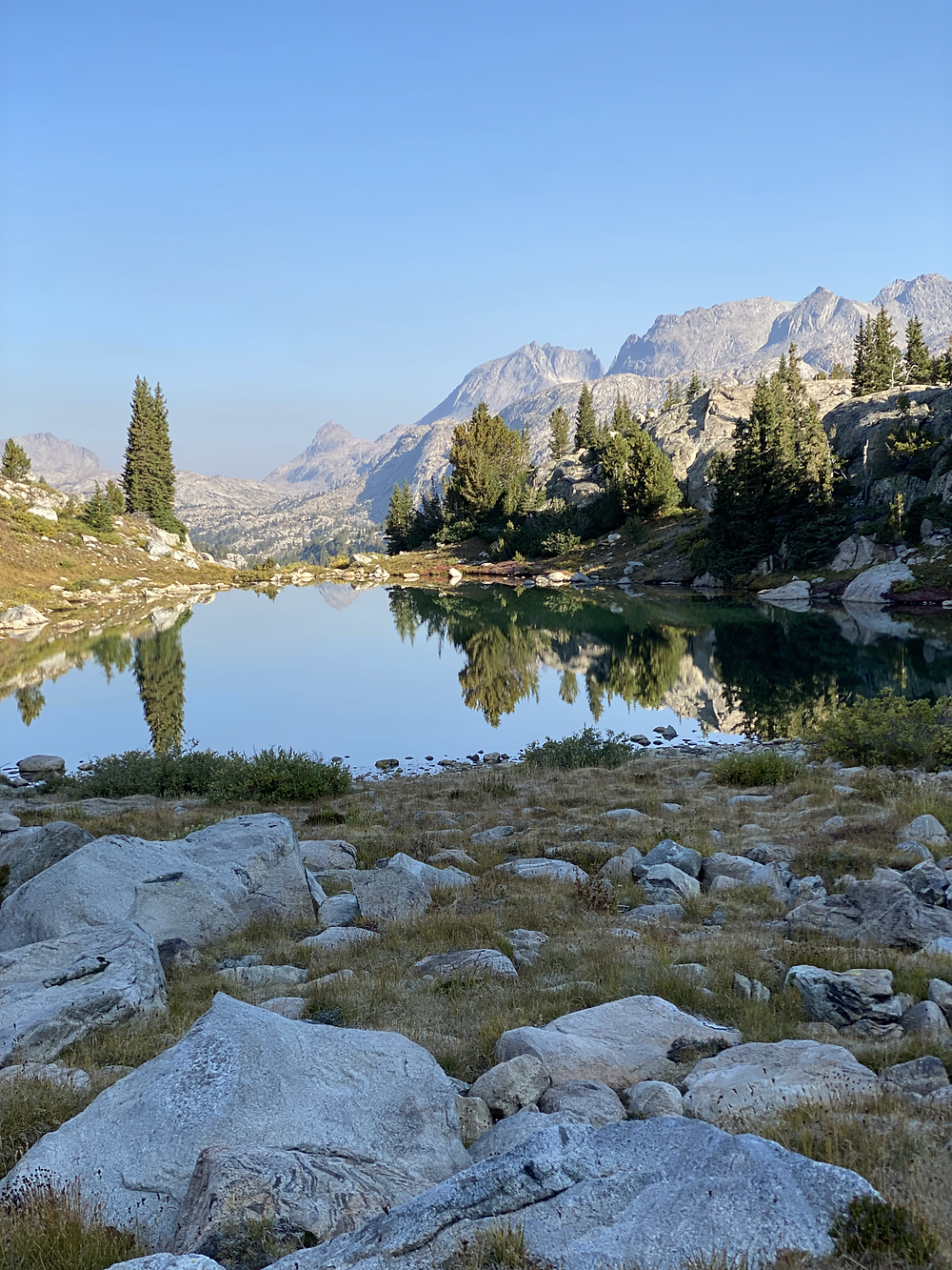 I feel these alt text snippets are getting rather repetitive, but every picture is a beautiful representation of a reflective mirror lake surrounded by mountains at Bridger-Teton National Forest in Wyoming
