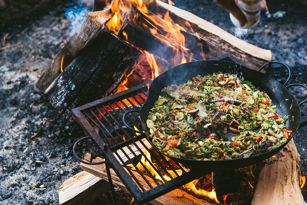 Argentine celebrity Chef Francis Mallmann prepares a feast in a cast iron skillet over an open fire. It looks delicious, but we have no idea what it actually is.
