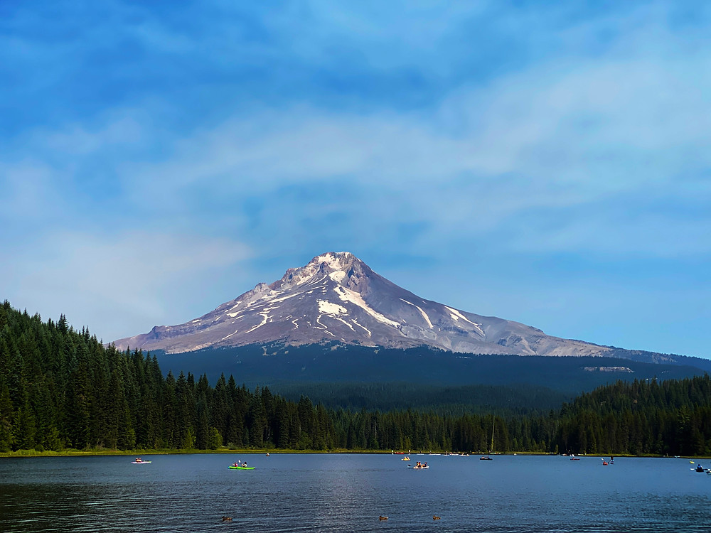 Mount Hood, dusted with snow, looms majestically over Trillium Lake as kayakers and other watersports lovers frolic below