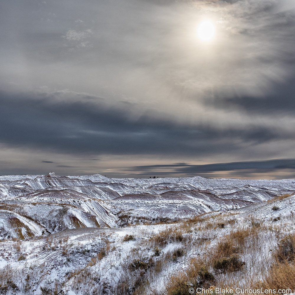 the craggy plains of Badlands National Park in South Dakota, covered in snow, under a grey cloudy sky that the sun is desperately trying to break through