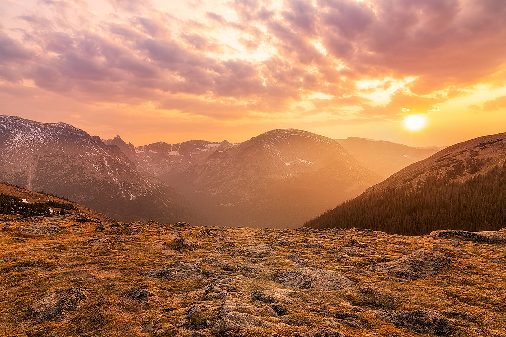 The sky burns as the sun sets over Ute Trail in Rocky Mountain National Park. Brilliant oranges, reds, and yellows splash across the sky over the mountains and rocks below.
