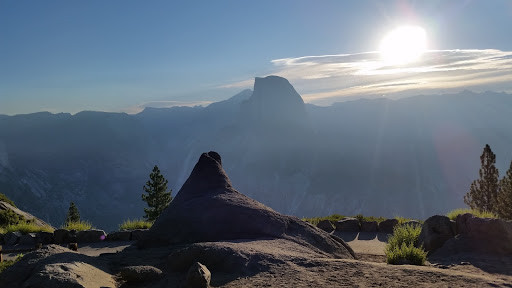 The sun beats through the haze on to Half Dome in the distance. In the foreground lies a rock shaped suspiciously like a reclining walrus