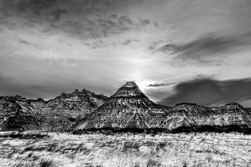 An eerie black and white photo of the striated cliffs of Bandlands National Park in South Dakota, with the sun illuminating the clouds