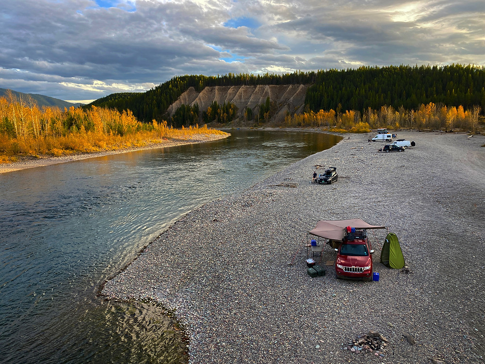 Vehicles set up for boondocking, camping for free on the banks of the Flathead River near Glacier National Park, Montana