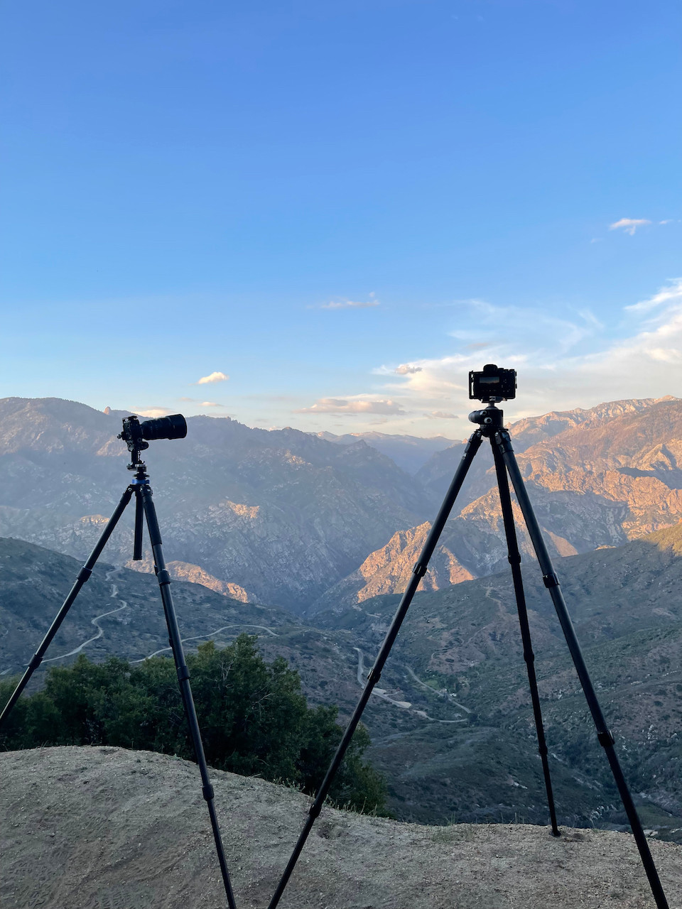 two cameras mounted on tripods stand triumphantly on a mountain ridge, ready to capture the glory of the lush hilly valley below