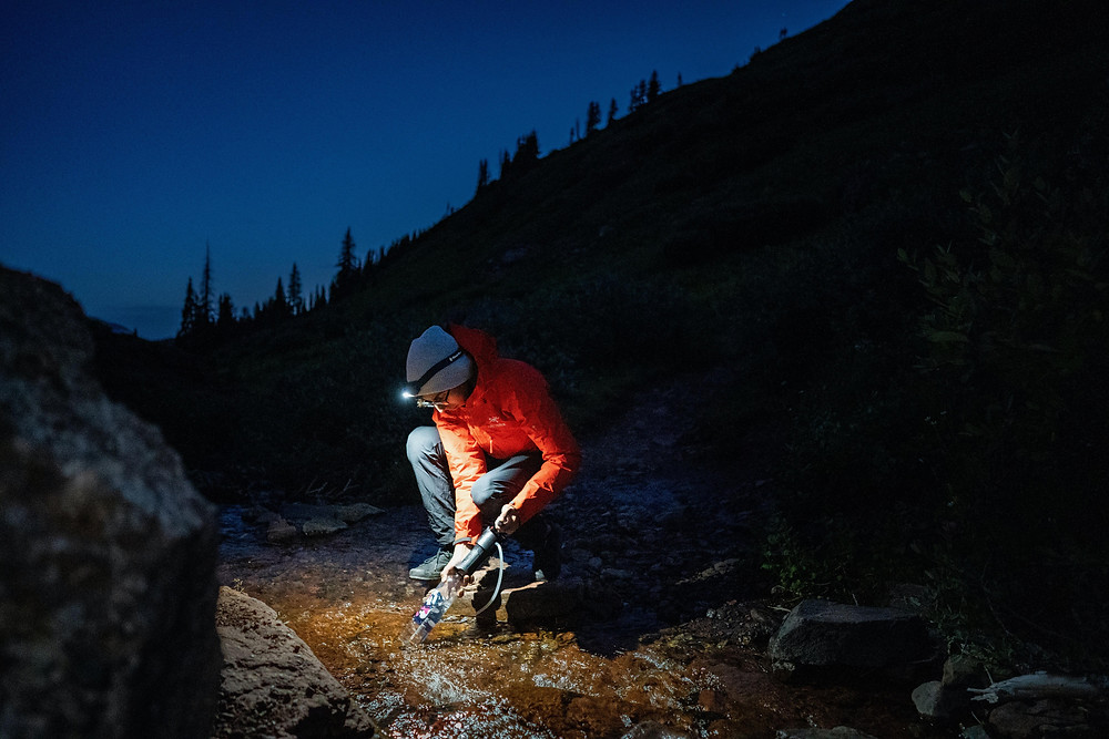 a man filters water from a stream by flashlight at night in the middle of the mountains