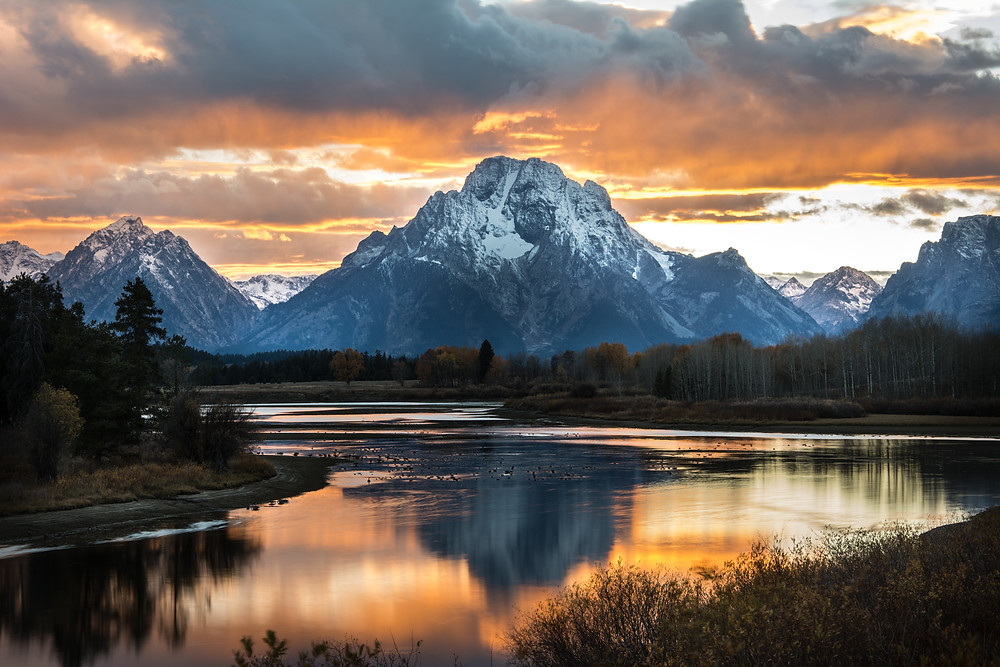 The orange skies over the Grand Tetons are reflected in the waters of Oxbow Bend