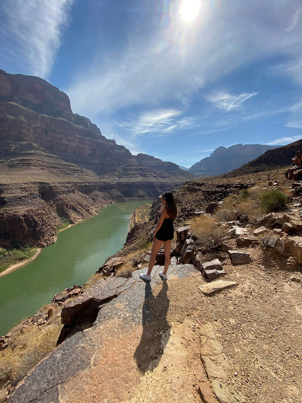 A woman gazes out over the green river and brown rocks of the Grand Canyon in Arizona