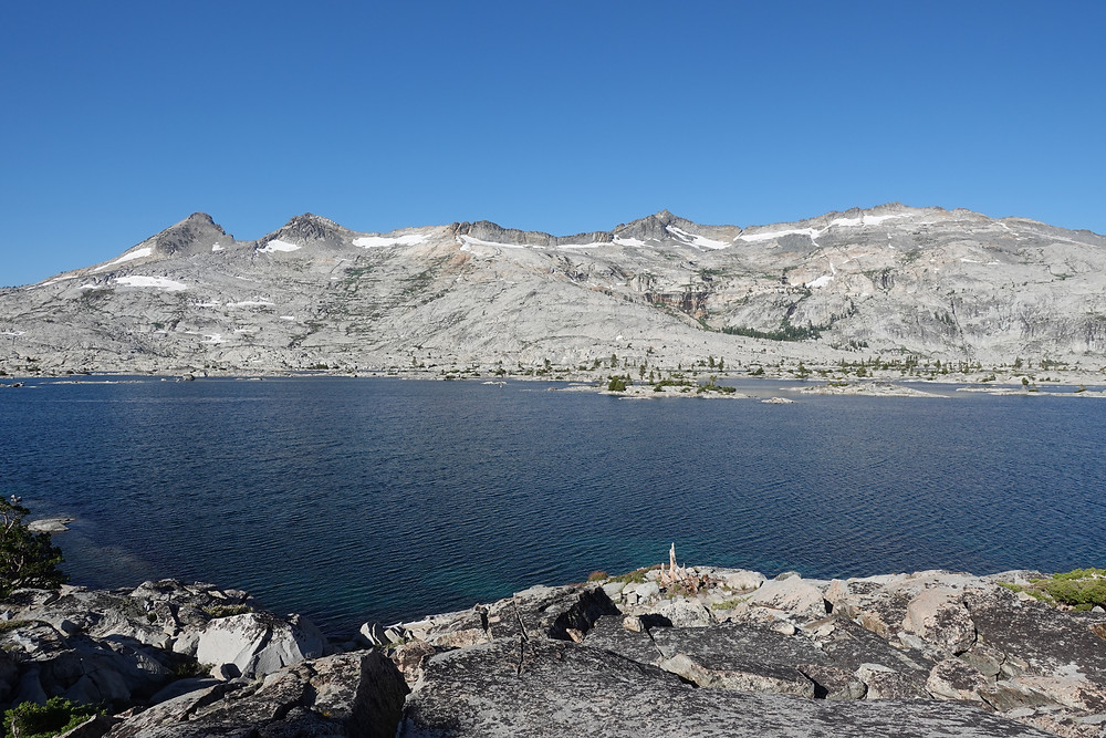 The water looks inviting, but extremely cold in a lake on the Tahoe Rim Trail. Is that snow o n the mountain across the lake?