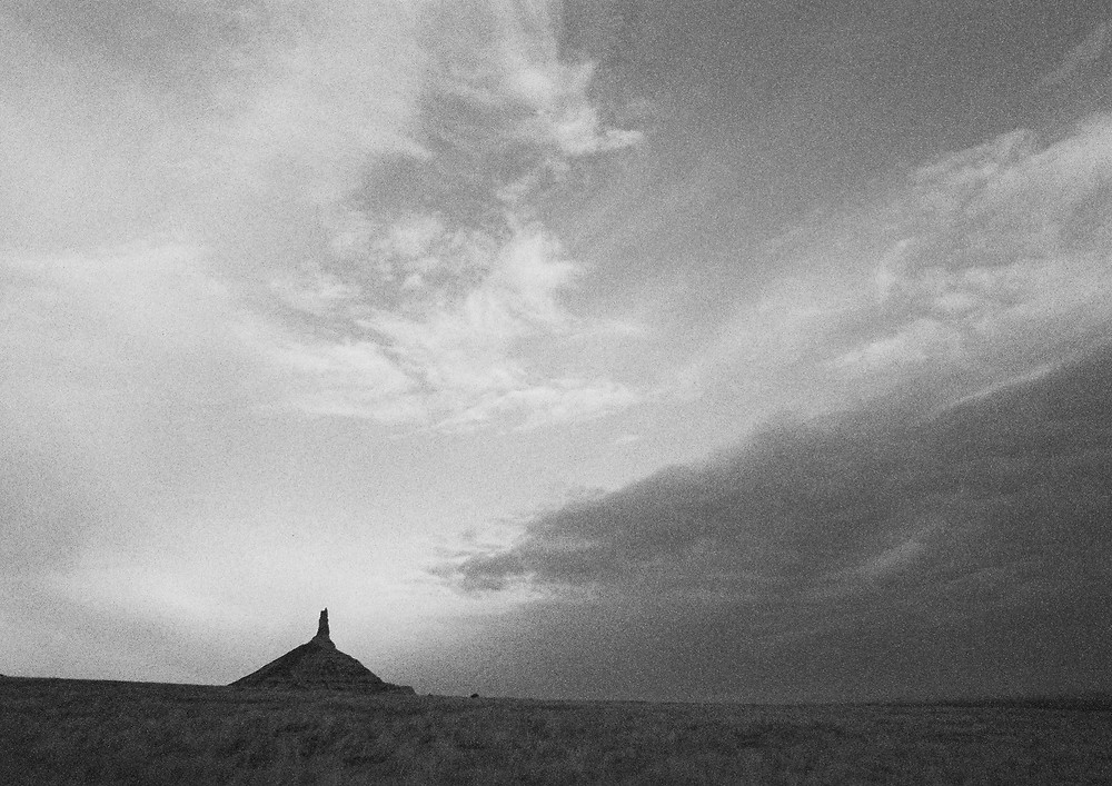 a black and white photo of clouds in the sky over Chimney Rock near Bayard, Nebraska