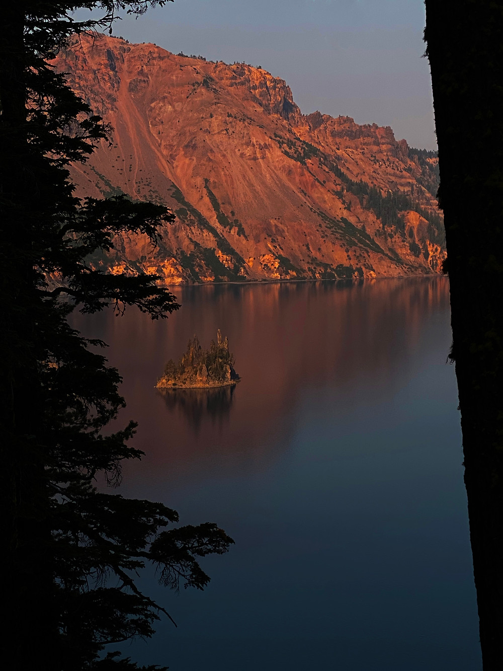 red mountains cascading into the crystal blue waters of Crater Lake in Oregon