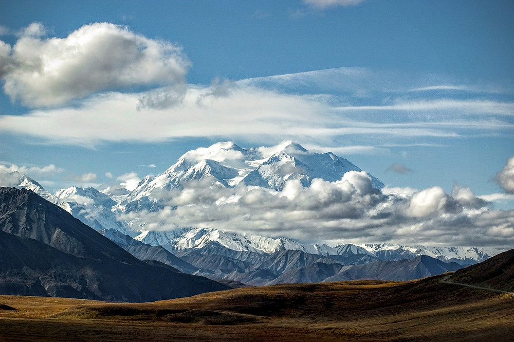 Snowy mountains rising majestically over the ridgeline at Denali National Park in Alaska