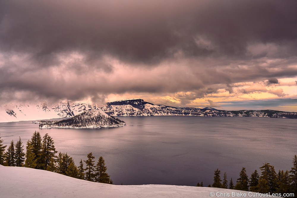 Stormy skies at sunset over Crater Lake in Oregon. Snow is everywhere