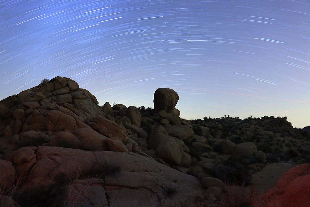 a timelapse photo of the starscape above the dark rocky craggy outlines of Joshua Tree National Park
