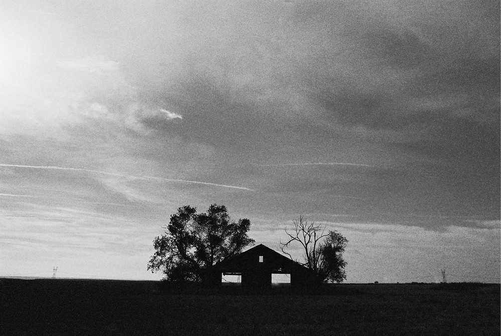 a black and white photo of clouds swirling over a spooky barn on the Great Plains of Nebraska