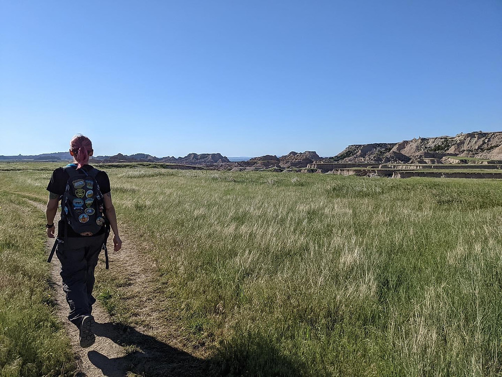 a woman with pink hair and dozens of National Park badges on her backpack hikes a trail through the grasslands of Theodore Roosevelt National Park in North Dakota