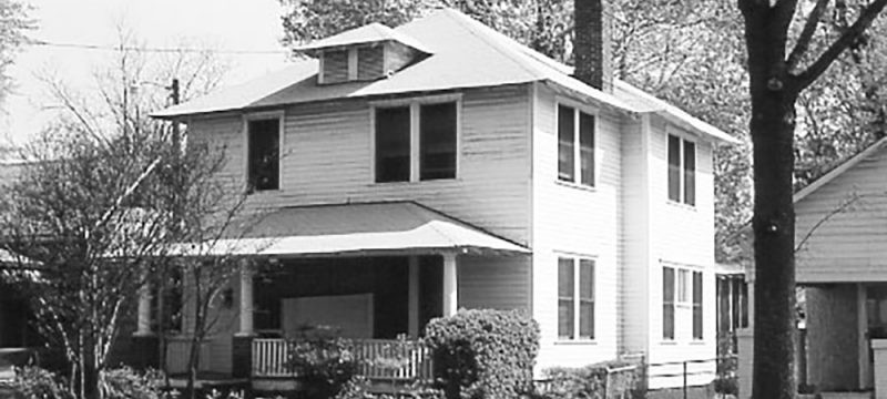 a black and white photo of Waberly Historic District in Columbia South Carolina. A two story house with an awning and a porch