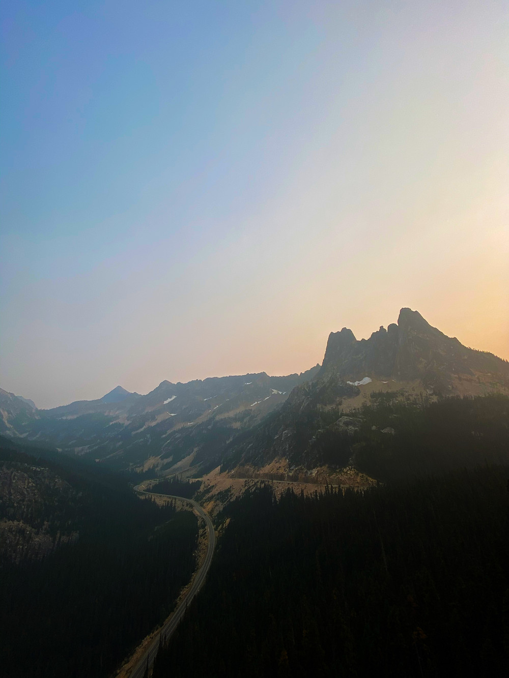 a haze settles over the sun setting on North Cascades National Park. Dark mountains loom as far as the eye can see, under hazy blue sky with the suggestion of an orange sunburst off to the right