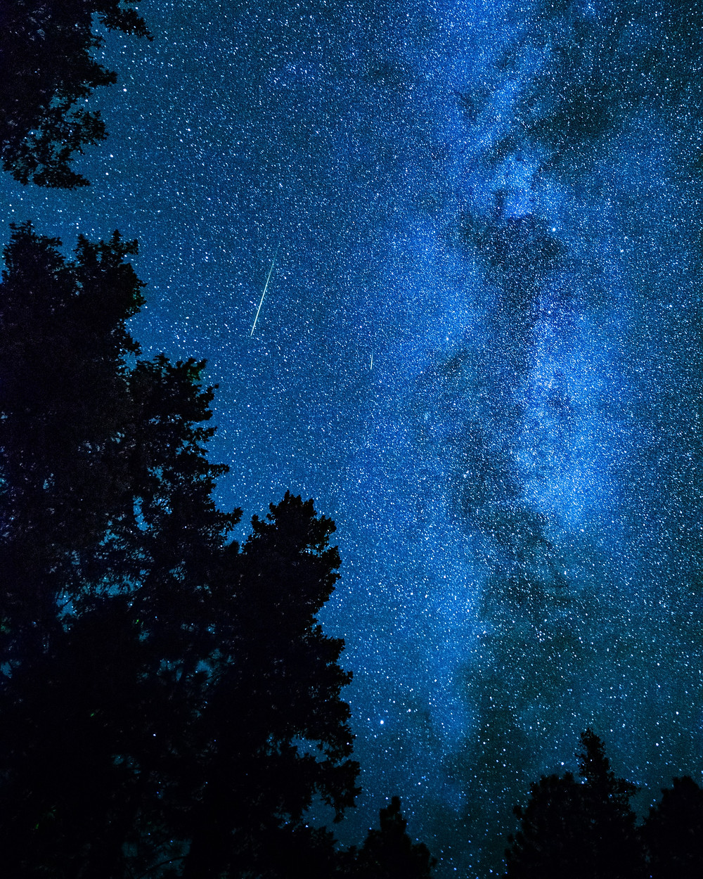 The night sky above the mountains of Washington is a deep blue, all the better for contrast for the meteor streaking overhead