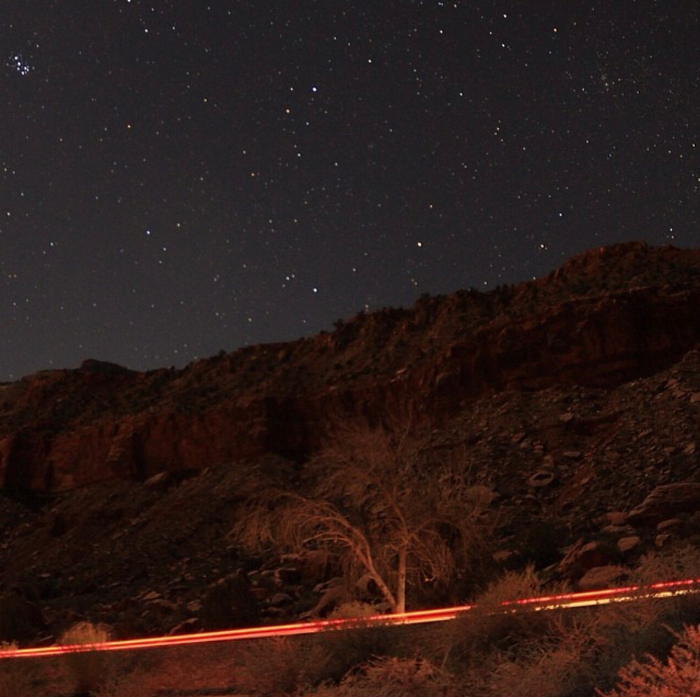 a brilliant black night sky illuminated with pinpoints of starry light, over the wooded ravine of Kern Canyon in southern California