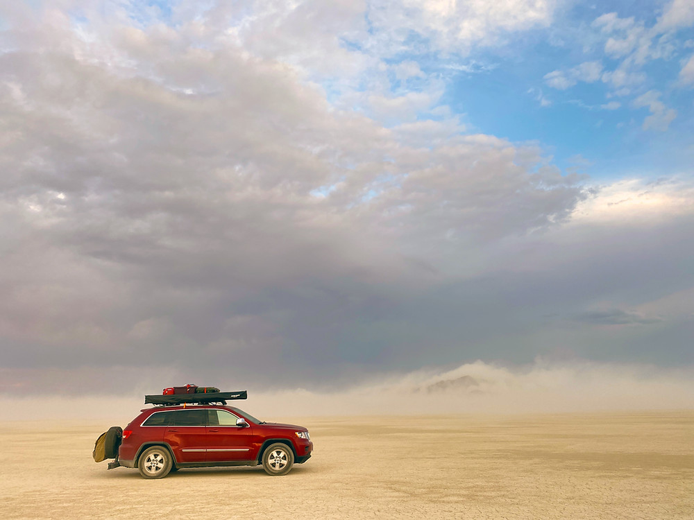 A dust storm blowing over Black Rock Desert in Northern Nevada, as a red 2011 Jeep Grand Cherokee outfitted for Van Life waits for the skies to clear