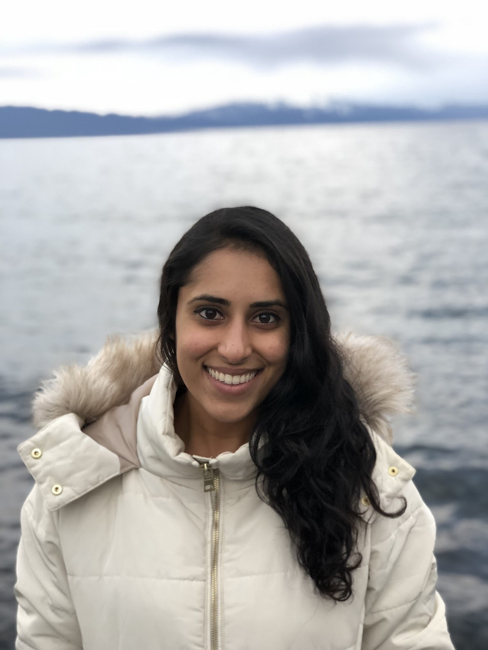 Guest blogger Ashima smiles for the camera wearing a white parka in front of a beautiful body of water