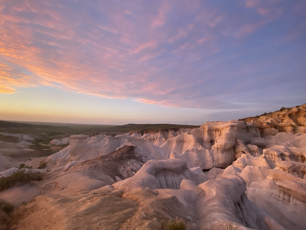 A brilliant sunset stains the clouds overhead the alien rock formations of Paint Mines Interpretive Park in Calhan, Colorado