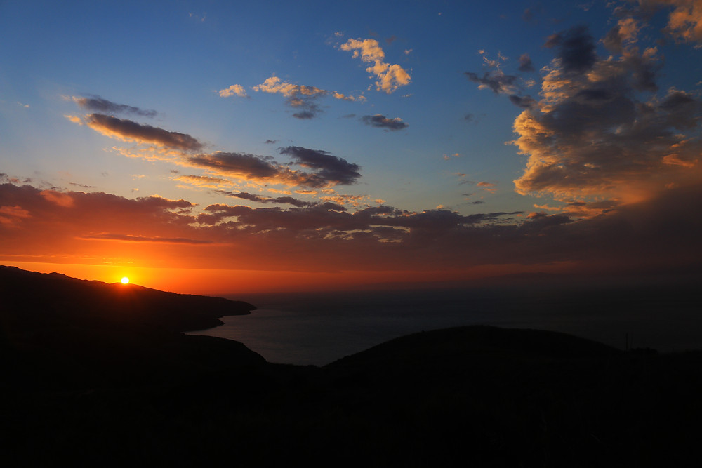 A brilliant sunset over Santa Cruz Island, part of Channel Islands National Park off the coast of Southern California. The setting sun glows orange as the island and ocean are shrouded in darkness.