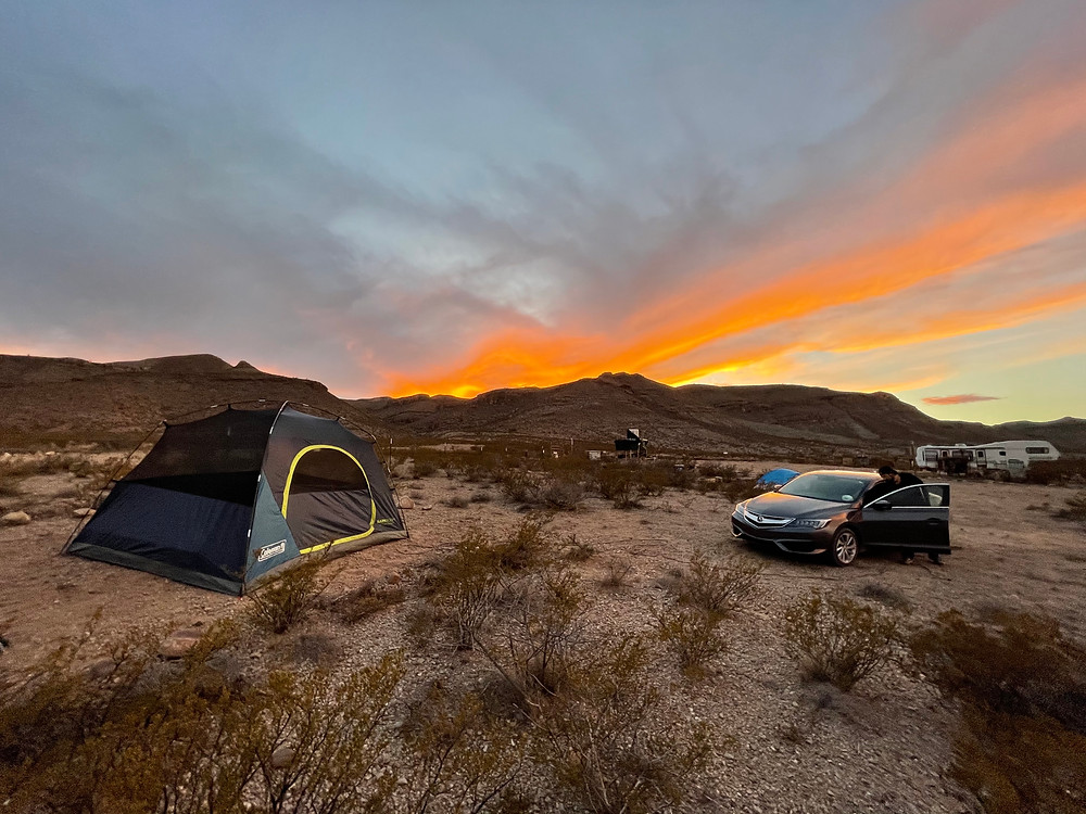 A dispersed campsite near Big Bend National Park. A tent is set up next to a car, with mountains in the distance the setting sun bursting oranges and blues off of the clouds overhead