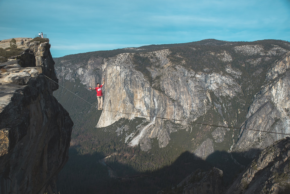 An insane badass walks a tightrope strung between Taft Point and God knows what else in Yosemite National Park in California