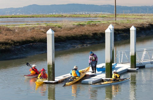 kayakers put into the still waters of Eden Landing in Union City, California via a boat landing ensconced by white pillars. A beautiful marshland stretches towards distant mountains in the background
